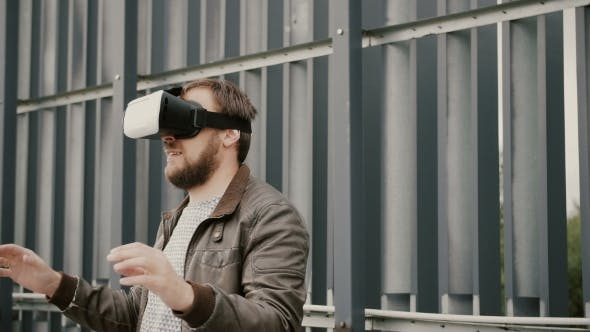 Thumbnail for Bearded Attractive Man Uses Virtual Reality Glasses In The Urban Space.