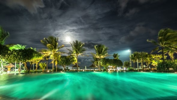 Cover Image for Illuminated Night Pool Against The Backdrop Of Palm Trees And The Sea.   - Bali, Indonesia, June