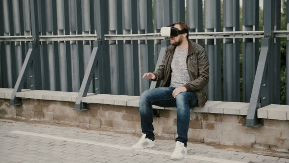 Thumbnail for Bearded Attractive Man Uses Virtual Reality Glasses On The Roof, Takes Off His Glasses And Walks