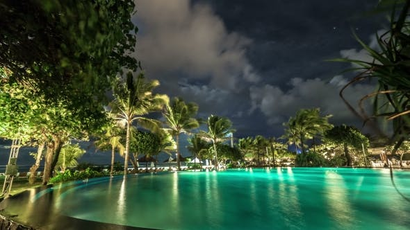 Thumbnail for Clouds Float Above The Illuminated Night Pool Against The Backdrop Of Palm Trees And The Sea.   -