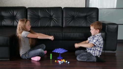 Brother And Sister Are Playing On The Floor