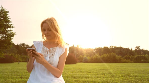 Thumbnail for Beautiful Girl Using Smartphone in the Park at Sunset 1
