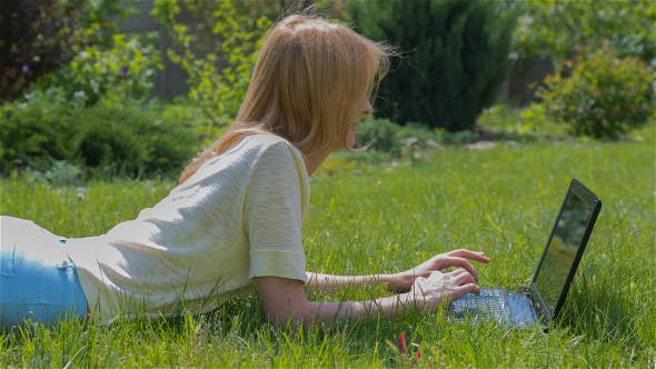 Thumbnail for Beautiful Girl Using Notebook Laying on Grass in Park 2