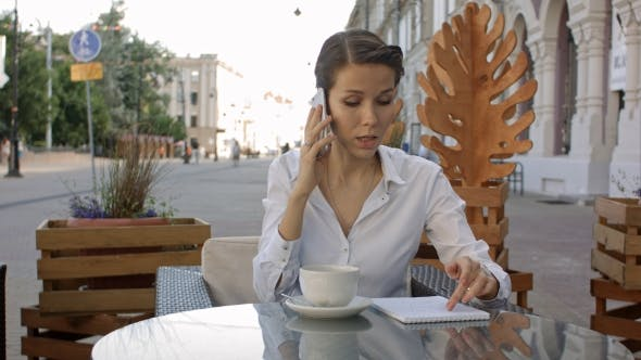 Thumbnail for Portrait Of Young Business Woman Sitting Relaxed At Outdoor Cafe Drinking Coffee And Calling Her
