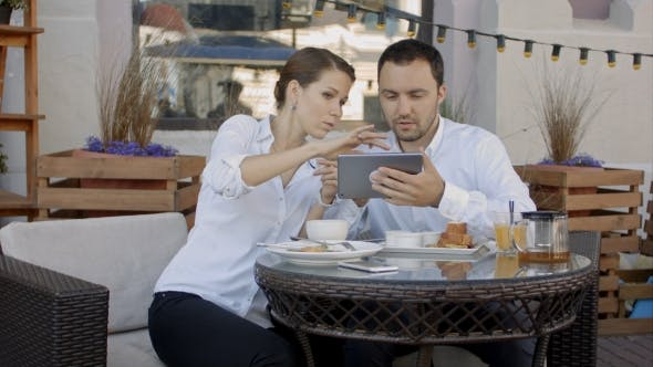 Thumbnail for Two Young Business People Using Digital Tablet On a Meeting At Coffee Shop