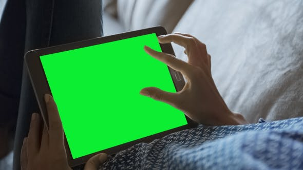 Cover Image for Beautiful Girl Using Tablet PC with Green Screen Laying on Sofa at Home 2