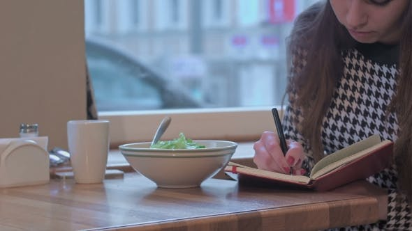 Thumbnail for Arms Of Young Businesswoman Writing In Note Book. She Is Sitting At The Table In Cafe And Eating a