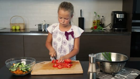 Thumbnail for Little cute girl cutting a tomato in the kitchen
