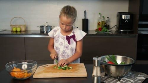 Little cute Girl  Preparing salad In The Kitchen