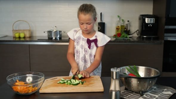 Thumbnail for Little cute girl cutting cucumber in the kitchen