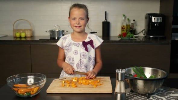 Thumbnail for Little cute girl cutting orange pepper in the kitchen
