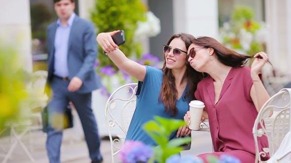 Thumbnail for Zwei junge Mädchen nehmen Selfie mit Smartphone im Freien Cafe. Zwei Frauen nach dem Einkaufen mit