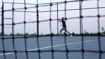 Tennis Net. Men Playing Tennis In The Background
