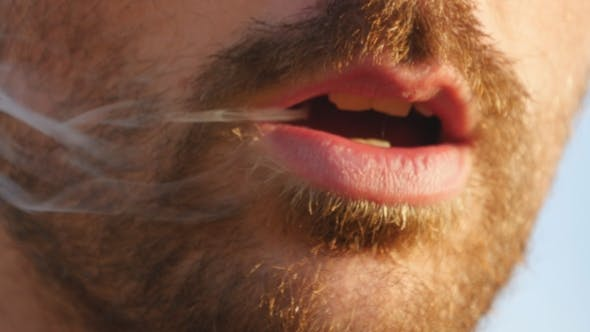 Thumbnail for Mouth of young man mouth smoking cigarette, smoke inhale, bad habit. Male mouth blowing smoke