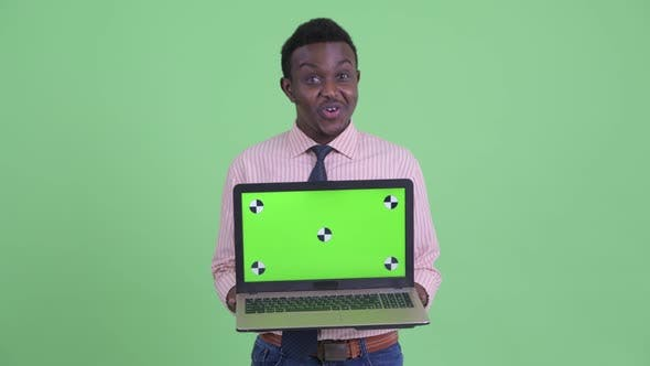 Happy Young African Businessman Showing Laptop and Looking Surprised
