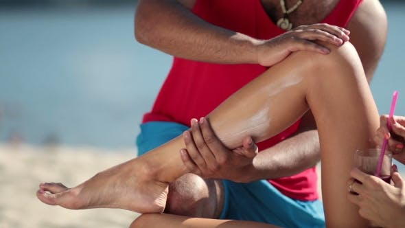 Thumbnail for Man's Hand Applying Sunscreen On Woman Leg