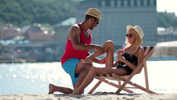 Thumbnail for Man Applying Sunscreen on Girlfriends Leg