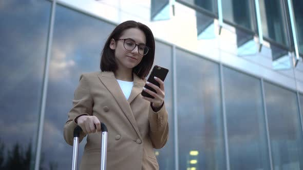 Thumbnail for A Young Woman Stands with a Phone on the Background of a Business Center. Girl in a Coat with a