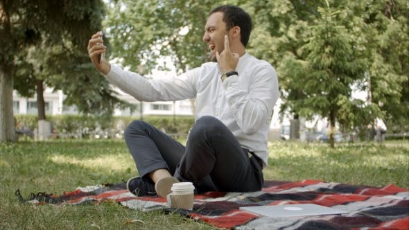 Thumbnail for Handsome Man Makes Selfie Photo In The Park, Sitting On The Grass