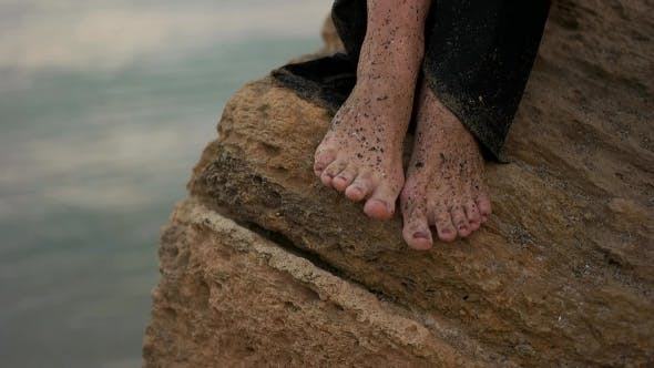 Thumbnail for Girls's Legs Sitting On The Rock At The Sea