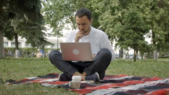 Thumbnail for Freelancer Man With Laptop At Summer Park On Bright Day. Man In Casual Working On His Notebook And