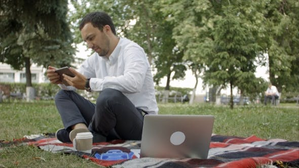 Thumbnail for Young Success Businessman Using Tablet, Laptop, Mobile Phone In The Park