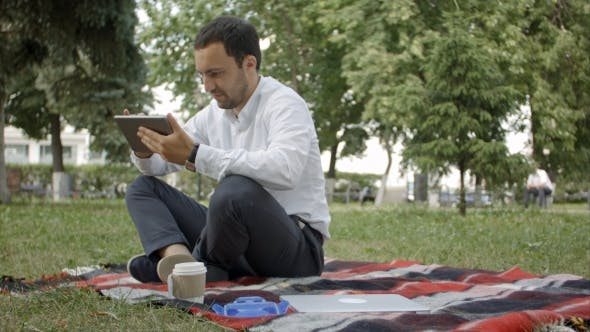 Thumbnail for Businessman At The Park With Tablet. Young Businessman At The Park Working With Tablet