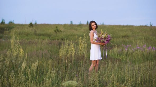 Thumbnail for Young Girl Walks On a Sunset On Summer Field With a Bouquet Of Flowers.