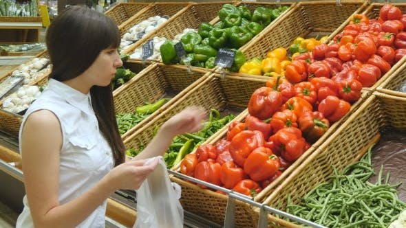 Thumbnail for Young Pretty Girl Is Choosing Peppers In a Grocery Supermarket. Attractive Woman Selecting Fresh