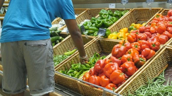 Thumbnail for Indian Man Is Choosing Peppers In a Grocery Supermarket. Guy Selecting Fresh Ripe Green Peppers In
