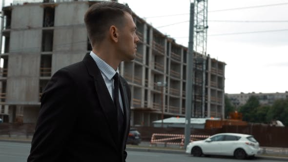 Thumbnail for Businessman In Suit Walking Near Newly Constructed Building
