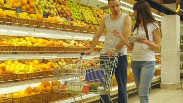 Thumbnail for Young Caucasian Couple Walking In a Supermarket With a Market Trolley And Choosing Fresh Apples. Man