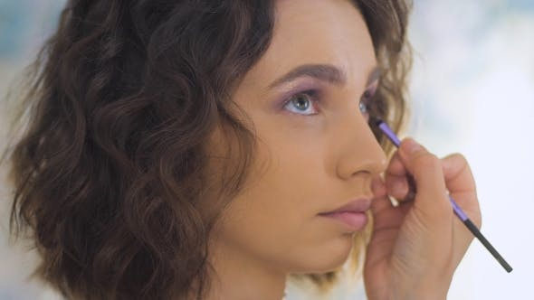 Thumbnail for Professional Makeup Artist Applying Make Up On a Beautiful Young Face For a Photoshoot