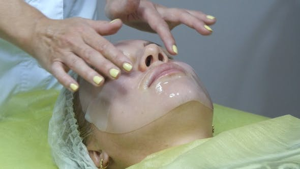 Thumbnail for Beautician Applying Facial Mask on a Beautiful Girl Face at a Beauty Salon