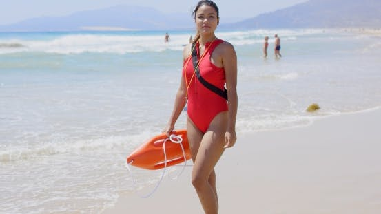 Thumbnail for Woman In Lifeguard Outfit On Beach With Swimmers