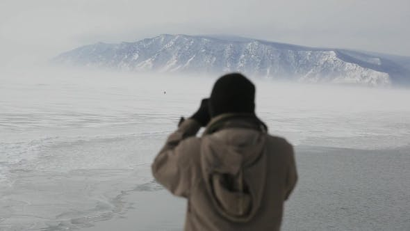 Thumbnail for A Tourist With a Camera Taking Pictures Of People On a Winter Lake From Mountains.
