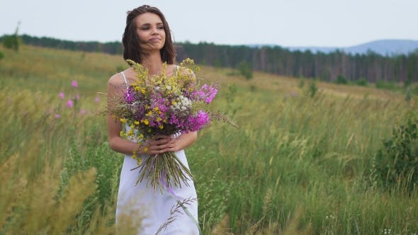 Thumbnail for One Young Woman Walking On Green Field Enjoying a Flower Bunch