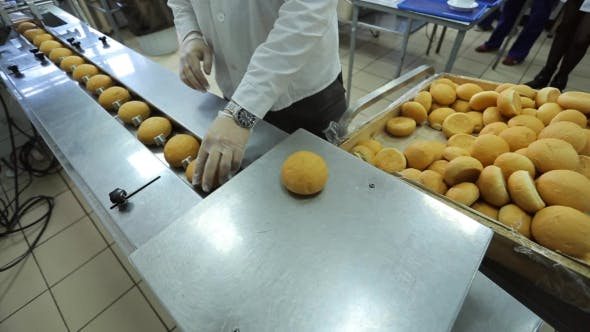 Thumbnail for Worker Puts Freshly Baked Rolls On Conveyor For Hermetic Packaging