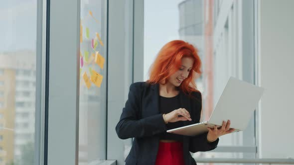 Thumbnail for Office Work with Laptop and Stickers. Young Red-haired Woman Holds a Laptop in Her Hand and Takes a