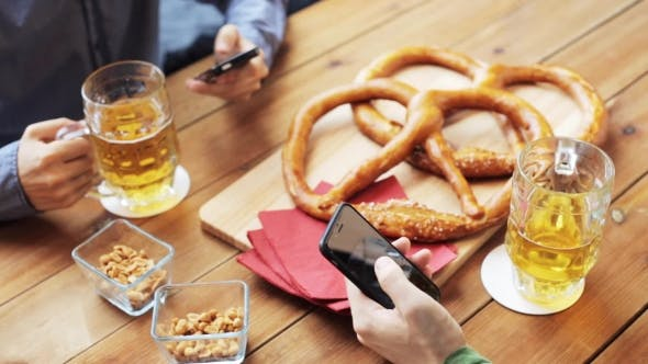 Thumbnail for Male Friends With Smartphones Drinking Beer At Bar