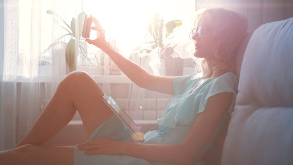 Thumbnail for Beautiful Girl with Tablet PC Making Selfie Sitting on Sofa Near Window 1