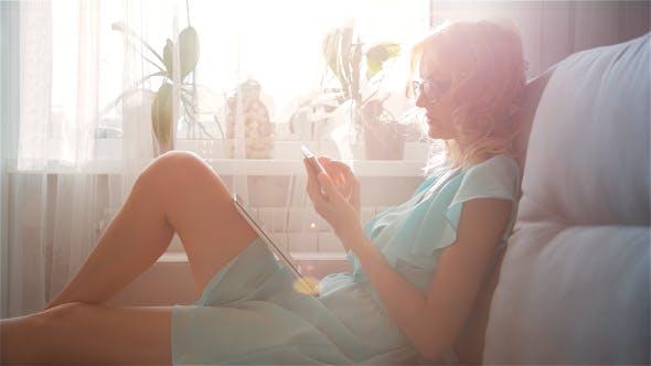 Thumbnail for Beautiful Girl Using Phone Sitting on Sofa Near Window 3