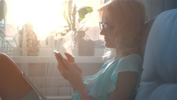 Thumbnail for Beautiful Girl Using Phone Sitting on Sofa Near Window 4
