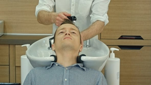 Thumbnail for Handsome Man Having His Hair Washed In Hairdressing Saloon. Young Man Lying With His Eyes Closed