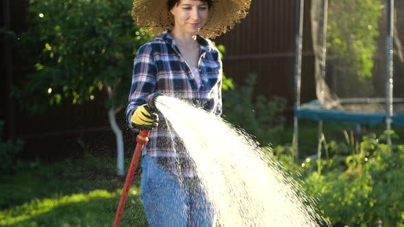 Thumbnail for Young Woman Watering Plants in Her Garden with Garden Hose. Hobby Concept
