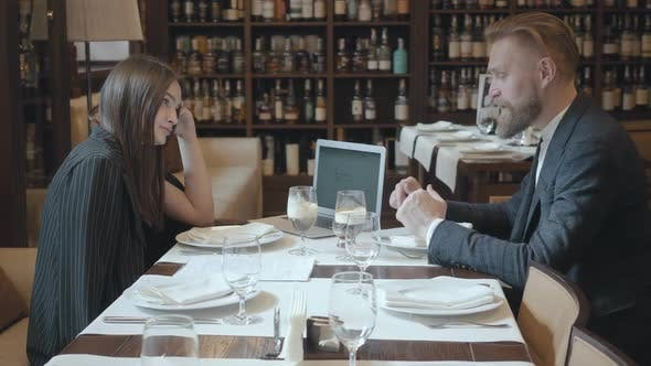 Thumbnail for Cute Young Beautiful Woman and Mature Man with Beard Having Business Dinner with Laptop Computer in