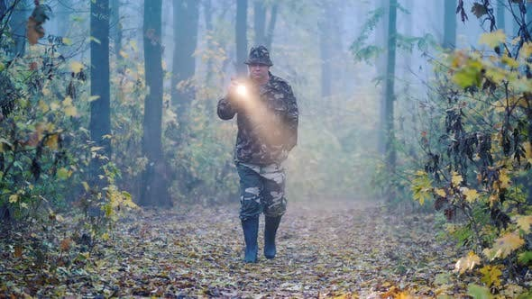 Thumbnail for A Man in Camouflage Is Walking Through the Forest, Lighting His Way in the Fog