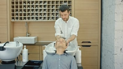 Barber Washing Client's Hair In Barbershop
