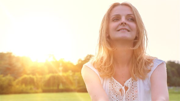 Thumbnail for Happy Beautiful Young Woman Sitting on the Grass in City Park and Smiling at Sunset 1