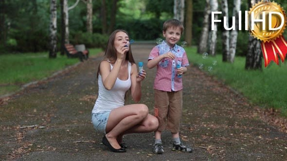 Mother and Son Blow Bubbles in Park